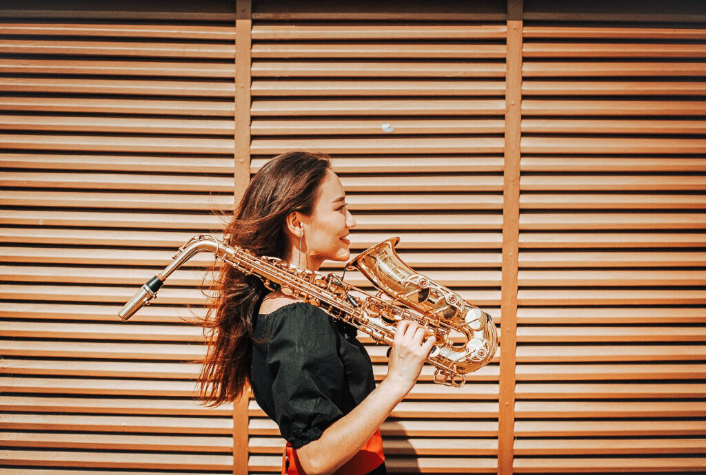 An Asian woman stands outside with a saxophone over her shoulder, smiling