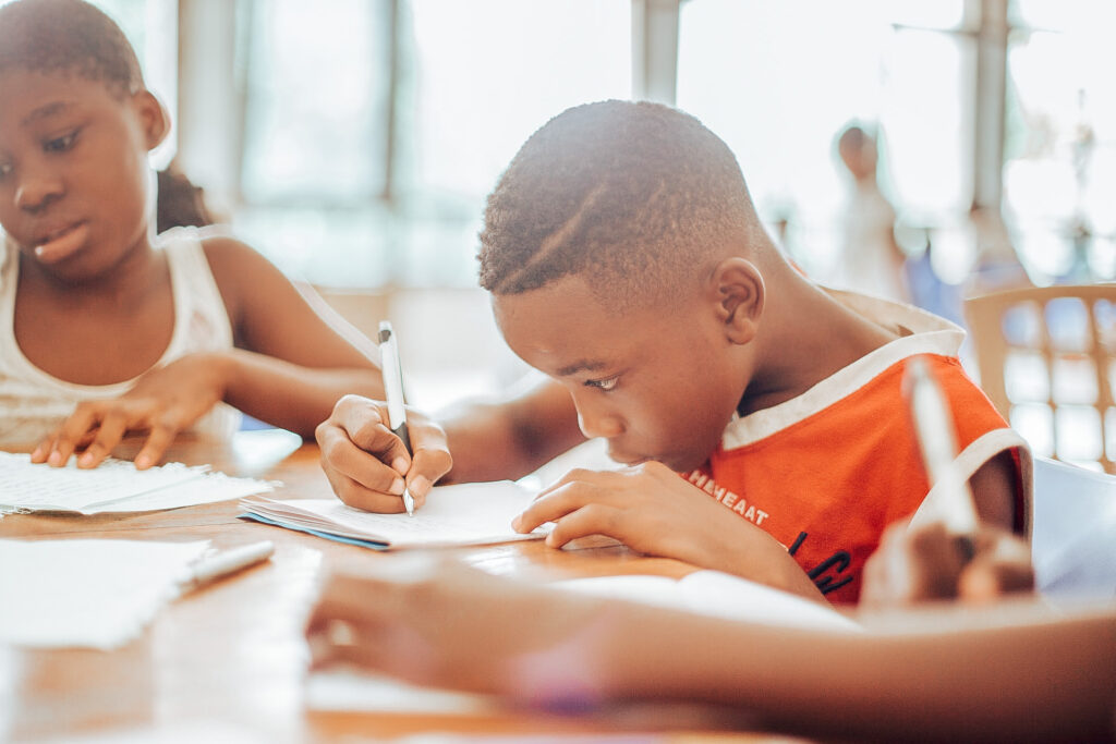 Two Black children sit the kitchen table doing school work, looking focused