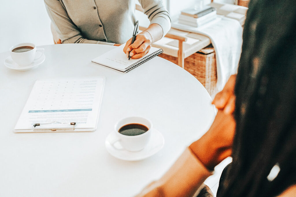 Two Black women sit at a table with coffee at an in-home interview